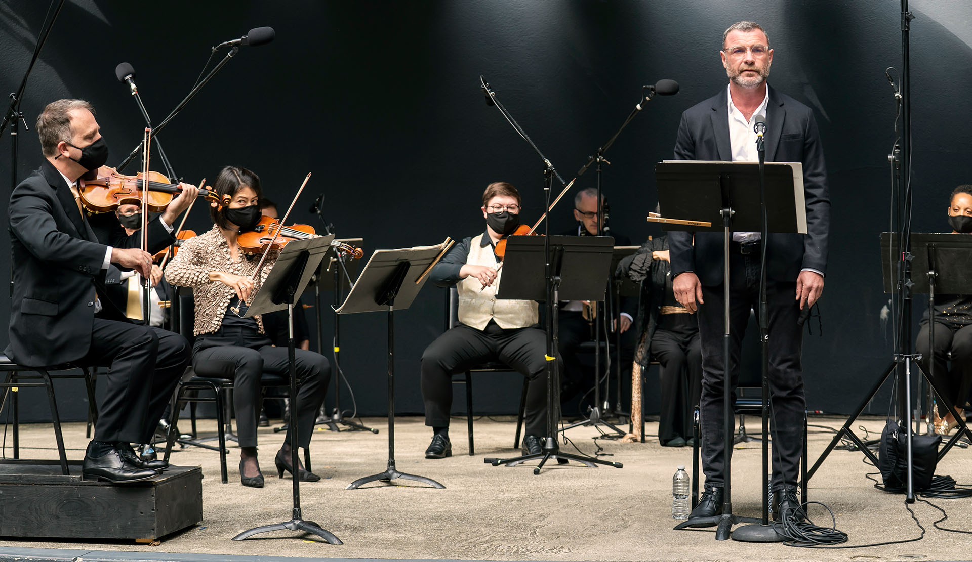 Liev Schreiber and members of Orpheus perform on stage against a black background