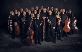 Orpheus Chamber Orchestra posed, standing with their instruments, in black clothing against a dark background